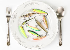 Porcelain plate with plastic fishing lures Royalty Free Stock Photo