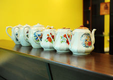 Porcelain pots stand in a row on the bar Royalty Free Stock Photography