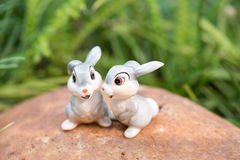 Porcelain rabbits with green grass background Royalty Free Stock Photography