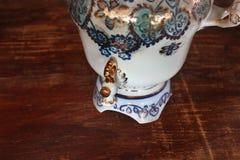 Porcelain samovar on a wooden background royalty free stock photography