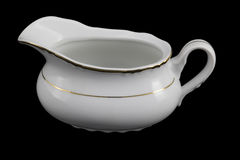 Porcelain sauce-boat on a black background Royalty Free Stock Images