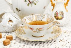 Porcelain set. Vase, sugar bowl with brown sugar,teapot and tea cup on the knitted lace tablecloth royalty free stock photography