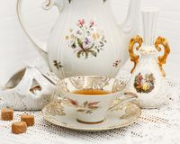 Porcelain set. Vase, sugar bowl with brown sugar,teapot and tea cup on the knitted lace tablecloth stock images