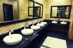 Row of wash basins with mirrors in a public toilet. Porcelain sinks and modern faucets for washing hands in a public toilet Stock Images