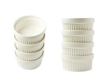 Porcelain souffle ramekin dish isolated. Pile of multiple white porcelain souffle ramekin dishes isolated over the white background, set of two different Royalty Free Stock Photos