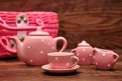 A porcelain spotted tea set with a pink basket. On a wooden background stock photos