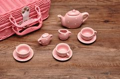 A porcelain spotted tea set with a pink basket. On a wooden background royalty free stock photo