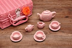A porcelain spotted tea set with a pink basket and an orange rose. On a wooden background stock photography