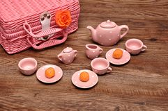 A porcelain spotted tea set with a pink basket and an orange rose. On a wooden background royalty free stock photo