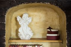 Porcelain statuette of an angel with wings and gift boxes in a niche in a brick wall stock photos