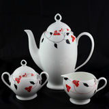Porcelain tea and coffee set. Jug, small cream jug and sugar bowl on a black background stock image