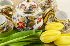 Porcelain tea and coffee set with yellow tulip flowers Stock Photo