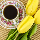 Porcelain tea cup with yellow tulip flowers Royalty Free Stock Image