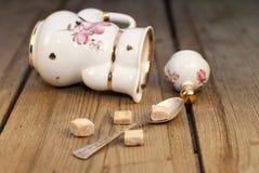 Porcelain tea pot with sugar cubes and handmade pillows Stock Photos