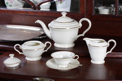 Porcelain tea set on old chest of drawers Stock Photography