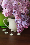 Porcelain teacup, lilac bouquet and white decors. On brown table Royalty Free Stock Photography