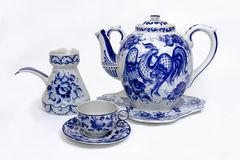 Porcelain teapot, cup, saucer and creamer in folk style painted blue on white background. Crockery in russian folk style royalty free stock images