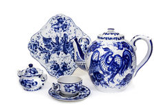 Porcelain teapot, cup, saucer, sugar bowl and dish in folk style painted blue on white background. Crockery in russian folk style royalty free stock images