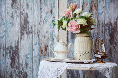 Porcelain teapot and cup on a table with a vase with artificial Royalty Free Stock Photo