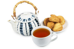 Porcelain teapot, cup of tea and biscuits on  saucer Royalty Free Stock Images