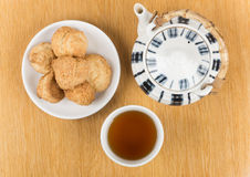 Porcelain teapot, cup of tea and biscuits on  saucer  on Stock Image