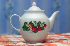 Porcelain teapot. With a pattern of strawberries on the table royalty free stock images