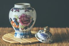 Porcelain vase with floral motif. Porcelain vase still life over dark background and wooden surface Royalty Free Stock Photography