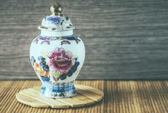 Porcelain vase with floral motif. Porcelain vase still life over wooden background and wooden surface Royalty Free Stock Photo