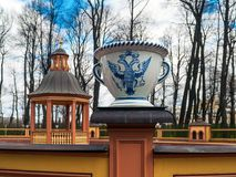 Porcelain vase with the royal coat of arms in a bosquet in the S. White porcelain vase with an imperial coat of arms in a bosquet, a pond in the Summer Garden in Royalty Free Stock Photos