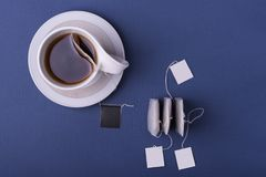 Porcelain white cup tea with three teabags on dark blue background. top view studio shot royalty free stock photography