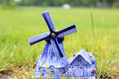 Porcelain windmill. With barn and flowers on the grass Stock Photo