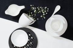 Porcelana blanca en manteles de lino blancos y negros. Foto de archivo libre de regalías