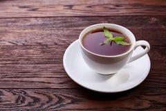 Porcelany biała chińska filiżanka czarna herbata i spodeczek z mennicą na roczniku zgłaszamy tło Zdjęcie Stock
