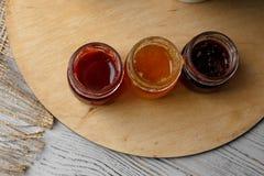 Porcelany teacup z zieloną herbatą i Naciskać róże na drewnianym stole Trzy małego słoju domowej roboty jagodowy dżem na zalecają Zdjęcia Stock