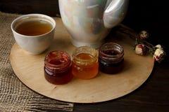 Porcelany teacup z zieloną herbatą i Naciskać róże na drewnianym stole Trzy małego słoju domowej roboty jagodowy dżem na zalecają Obrazy Royalty Free