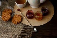 Porcelany teacup z zieloną herbatą i Naciskać róże na drewnianym stole Trzy małego słoju domowej roboty jagodowy dżem na zalecają Obraz Stock