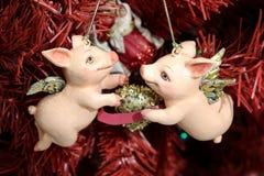 Porcelets de Noël de cupidon tenant le coeur d'or sur l'arbre rouge Image libre de droits
