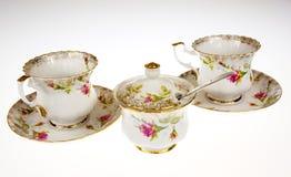 Porcellana due, tazze decorative e zucchero-ciotola su bianco isolato Fotografie Stock Libere da Diritti