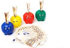 4 porcellini salvadanaio con le euro note Fotografia Stock
