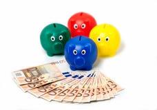4 porcellini salvadanaio con le euro note Immagini Stock