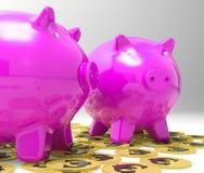 Porcellini salvadanaio sulle euro monete che mostrano ricchezza Immagine Stock