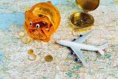 Porcellino salvadanaio arancio con i soldi di risparmio per viaggiare Fotografia Stock