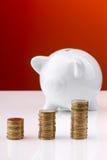 Porcellino salvadanaio bianco con la pila di monete Immagine Stock