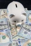Porcellino salvadanaio bianco su un mucchio di valuta degli Stati Uniti contro un fondo nero fotografie stock