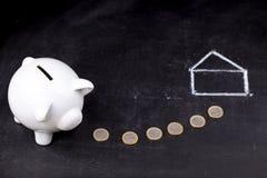 Porcellino salvadanaio bianco sulla lavagna: risparmio per una casa Immagini Stock