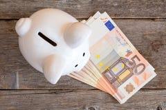 Porcellino salvadanaio con 50 euro fatture Fotografia Stock