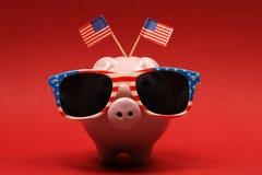 Porcellino salvadanaio con gli occhiali da sole con la bandiera di U.S.A. e due piccole bandiere di U.S.A. su fondo rosso Fotografia Stock