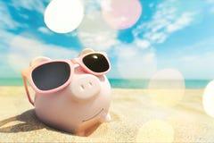 Porcellino salvadanaio con gli occhiali da sole sulla sabbia della spiaggia Fotografie Stock