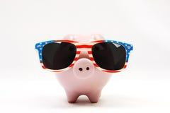 Porcellino salvadanaio con i retro occhiali da sole con la bandiera di U.S.A. Fotografia Stock