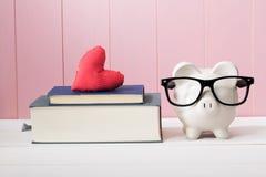 Porcellino salvadanaio con i vetri accanto ai libri con cuore Immagine Stock